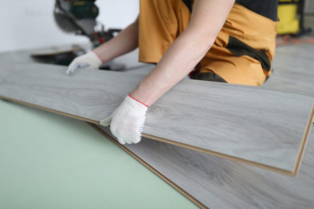 Worker installing timber floor panels