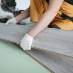 Worker installing timber floor panels